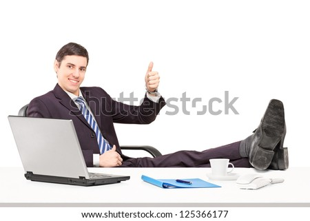 Young businessperson sitting on a chair with his legs up and giving a thumb up isolated on white background