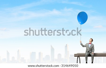 Young businessperson sitting on a wooden bench and relaxing - stock photo