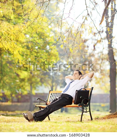 Young businessperson sitting on a wooden bench and relaxing in a park, shot with tilt and shift - stock photo
