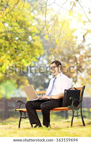Young businessperson sitting on a wooden bench and working on a laptop in a park - stock photo
