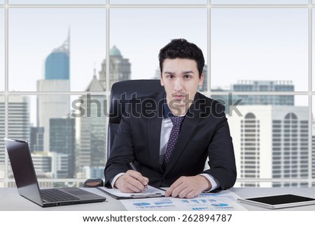 Young businessperson writing on the clipboard while looking at the camera in the office room