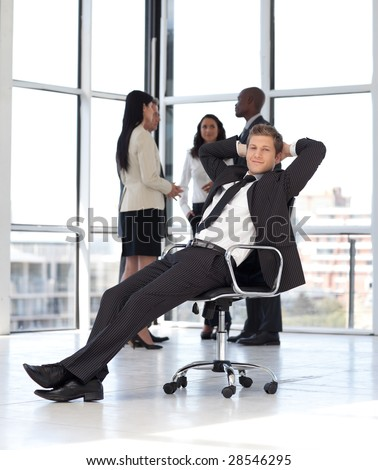 Young Businesssman in office sitting on chair - stock photo