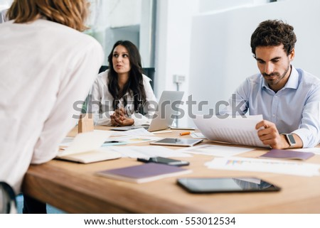 Young businesswoman and businessman during a meeting in office to launch start-up. They speak, show graphs and charts