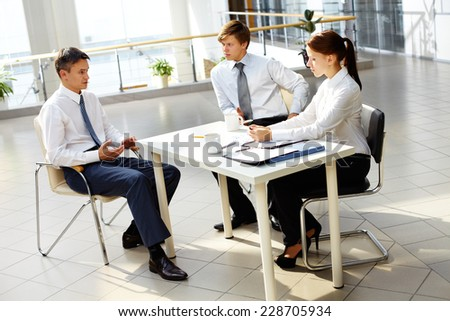 Young businesswoman and businessman looking at their boss explanations at meeting  - stock photo