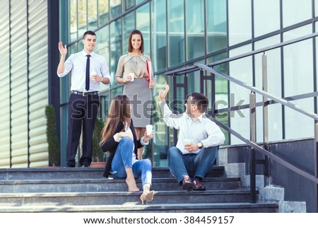 Young businesswoman and businessman sitting on the steps of the office building and drinking coffee while their two colleagues are approaching and greeting them.