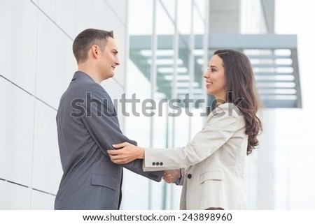 Young businesswoman and businessmen shaking hands - stock photo