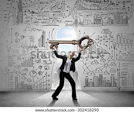 Young businesswoman and keyhole at background lifting big key above head - stock photo