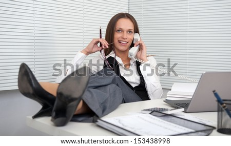 young businesswoman answering telephone with her legs on the table