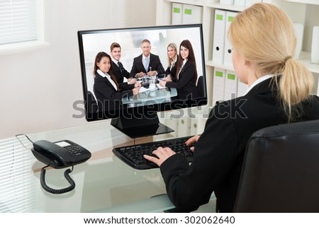 Young Businesswoman At Desk Video Conferencing With Colleagues On Computer In Office - stock photo