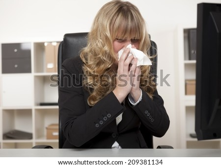 Young businesswoman blowing her nose as she sits at her desk at work suffering from seasonal hayfever, a cold or influenza - stock photo