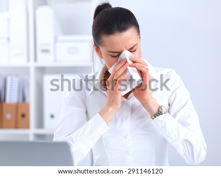 Young businesswoman blowing her nose, sits at her desk . - stock photo