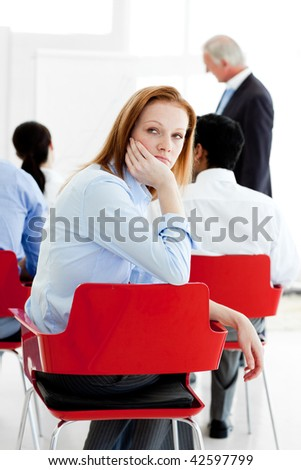 Young businesswoman bored at a conference with her colleagues - stock photo