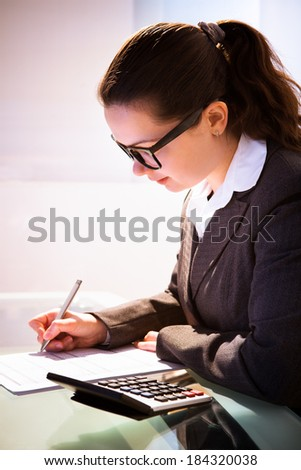 Young businesswoman calculating tax at desk in office