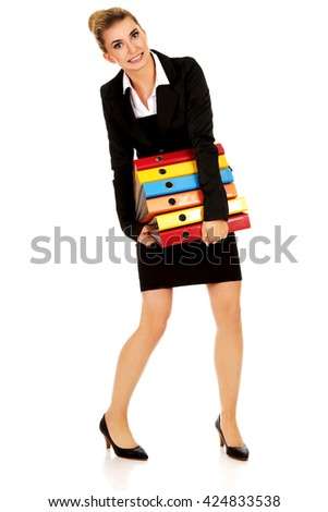 Young businesswoman carries heavy binders - stock photo