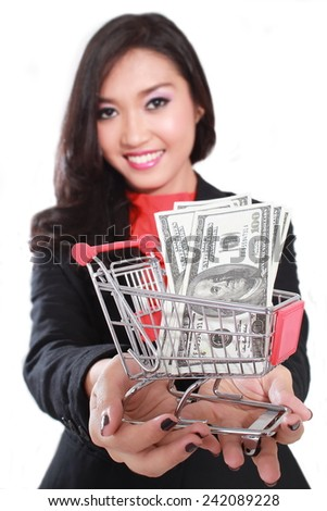 young businesswoman carrying a shopping cart containing a lot of money dollars, isolated on white background - stock photo