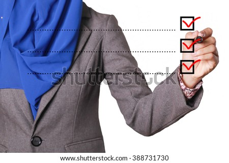 Young businesswoman checking mark on checklist with pen - stock photo