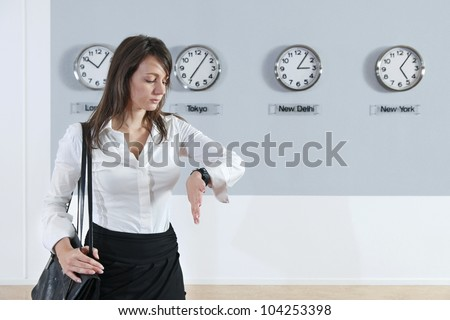 Young businesswoman checking time with world time zone clocks in background - stock photo