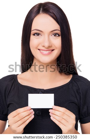 Young businesswoman cheerfully smiling and holding blank card, isolated on white background - stock photo