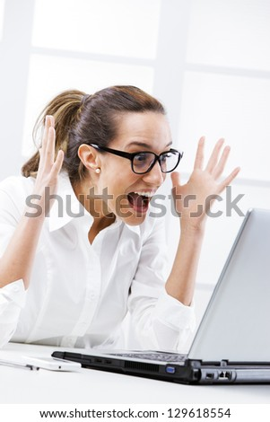 Young businesswoman cheering, screaming at laptop