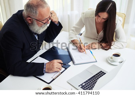 Young businesswoman consulting documents and ideas with her colleague - stock photo