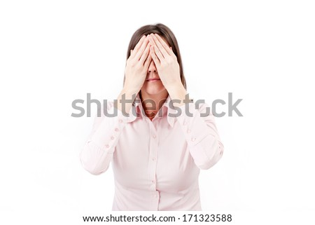 Young businesswoman covering her eyes with hands.