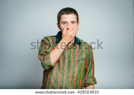 young businesswoman covers her mouth with his hands, isolated on a gray background