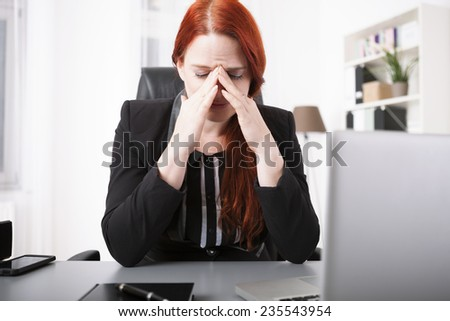 Young businesswoman crying on desk - stock photo