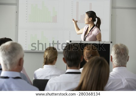 Young Businesswoman Delivering Presentation At Conference - stock photo