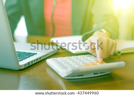 young businesswoman doing financial calculation at desk in office - stock photo