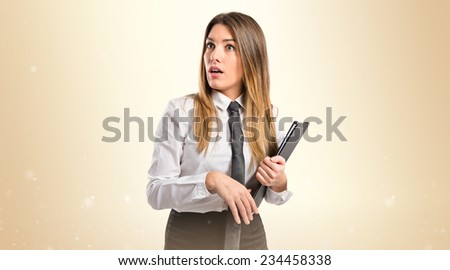 Young businesswoman doing surprise gesture over ocher background  - stock photo