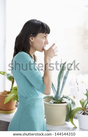 Young businesswoman drinking water by plants in home office - stock photo
