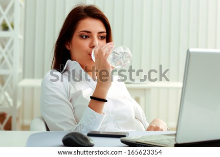 Young businesswoman drinks water on her workplace in office - stock photo