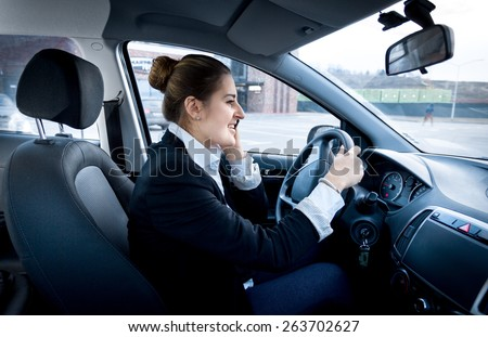 Young businesswoman driving a car and talking by phone