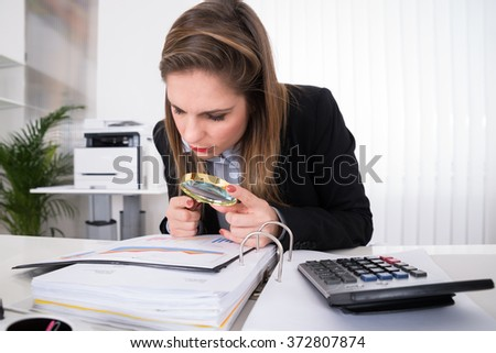 Young Businesswoman Examining Invoice With Magnifying Glass At Desk - stock photo