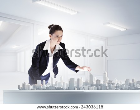 Young businesswoman examining model of construction project - stock photo