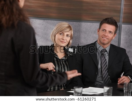 Young businesswoman explaining business problem, others sitting at meeting table, looking at her.? - stock photo