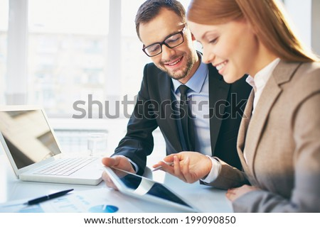 Young businesswoman explaining report to her colleague at meeting - stock photo