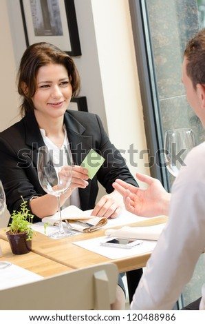Young businesswoman giving a business card during lunch time
