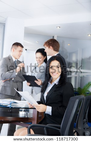 young businesswoman happy smile. Sitting at the desk at office with group of business colleagues people in the background businesspeople working in team at meeting, woman looking at camera - stock photo