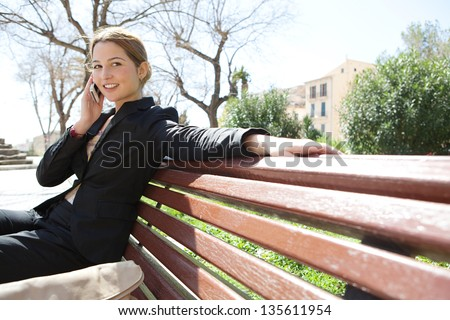 Young businesswoman having a conversation using a smartphone on a phone call while sitting on a city park bench, smiling.