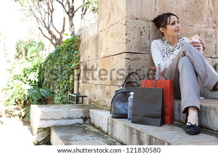 Young businesswoman having a lunch break and eating a sandwich while sitting on a park's stone steps with textured stone walls around her.