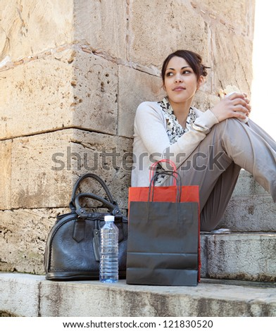 Young businesswoman having a lunch break and eating a sandwich while sitting on stone steps with textured stone walls around her. - stock photo