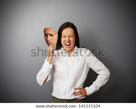 young businesswoman hiding her anger behind the mask of sad mood - stock photo