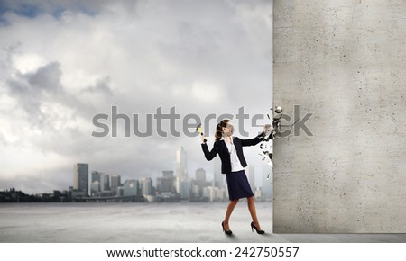 Young businesswoman hitting nail in wall with hammer