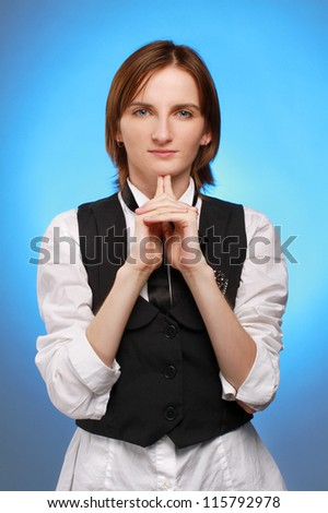 Young businesswoman hold her finger at her chin, studio shoot on blue background - stock photo
