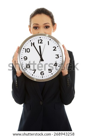 Young businesswoman holding a big clock. - stock photo