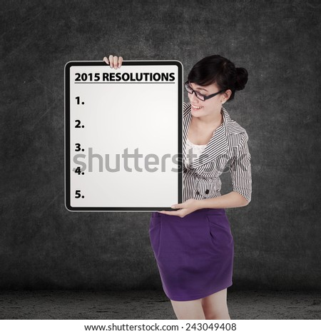 Young businesswoman holding a board to write a list of business resolution in 2015 - stock photo