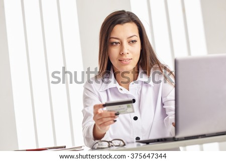 Young businesswoman holding a credit card and looking at the laptop. - stock photo