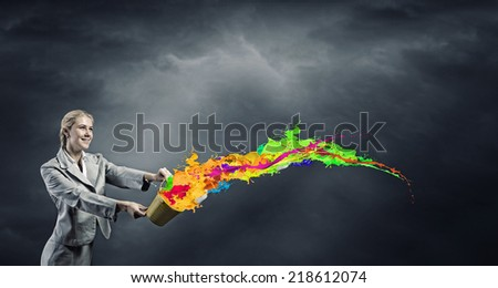 Young businesswoman holding bucket with paint splashes - stock photo