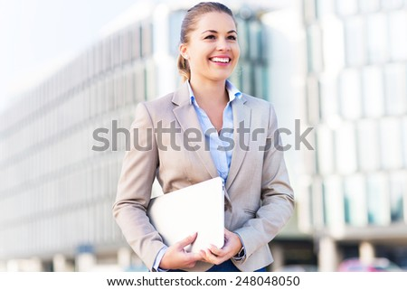 Young businesswoman holding laptop  - stock photo